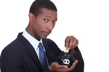 Man putting coins in piggy bank