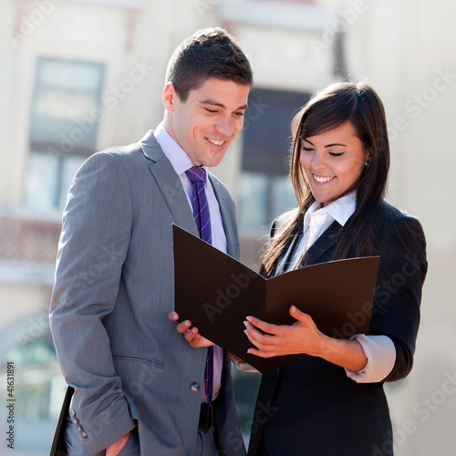 Business couple outdoors with files.