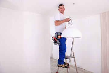 Handy-man fixing ceiling light