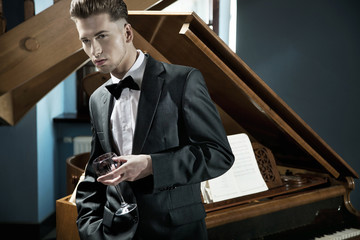 Young pianist with glass of wine
