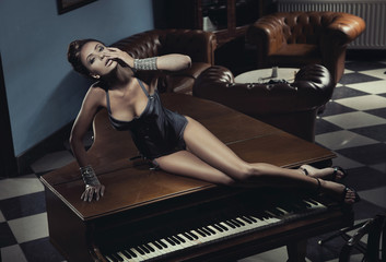 Sexy actress laying on a piano