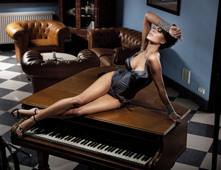 Young sexy woman laying on a piano