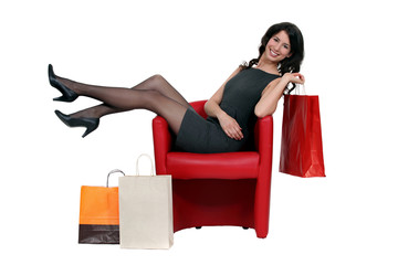 Brunette sat in chair with shopping bags