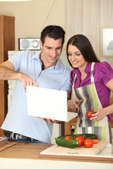 Couple cooking with a laptop