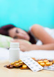 Sick woman in bed and pills on her bedroom table