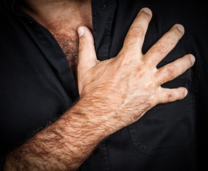 Chest pain concept - Hand touching chest