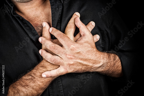 Chest pain concept - Two hands touching chest