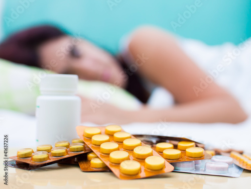 Sick woman in bed and pills from her medical treatment