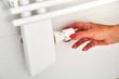 Frauenhand dreht die Heizung auf