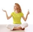 Woman with energy-saving bulb sitting cross-legged on floor.
