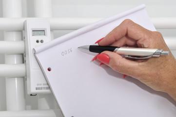 Frauenhand schreibt Heizungsverbrauch auf einen Block