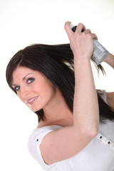 Woman spraying a beauty product into her hair