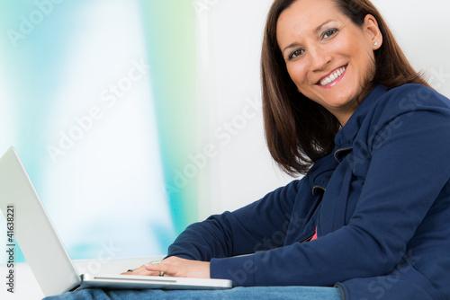 glückliche brünette frau mit ihrem laptop