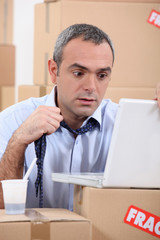 Panicking man using a laptop surrounded by boxes