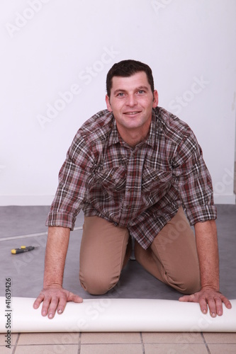 Man unrolling carpet