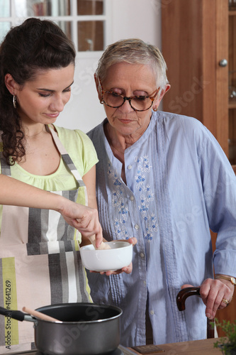 Young woman cooking with her grandmother