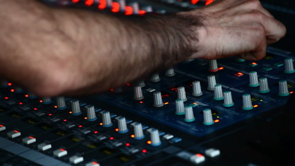 Man in sound studio working with sound mixer console
