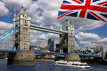 Tower Bridge with boat and  flag of England in London