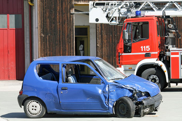car destroyed in a traffic accident and trucks of firefighter