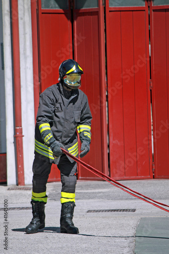Fireman while unrolls a fire hose to extinguish the flames