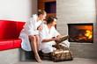 Junges Paar sitzt im Bademantel vor dem Kamin
