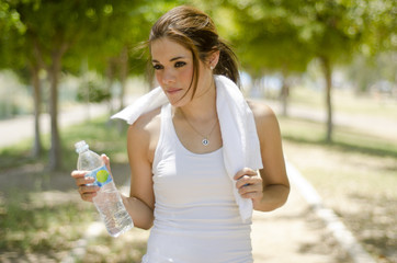Young woman drinking water while exercising