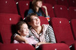 Loughing mother and daughter at the cinema
