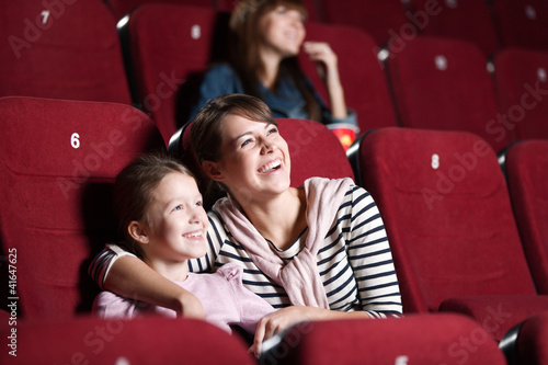 Leinwanddruck Bild Loughing mother and daughter at the cinema