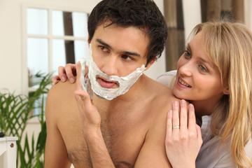 Man shaving in his bathroom