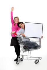 Children in a shopping trolley with a blank board