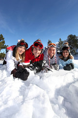 Four friends laying in the snow