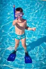 A little boy standing in a pool