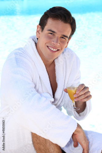 Young man drinking a glass of orange juice