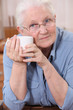 Old lady drinking from mug