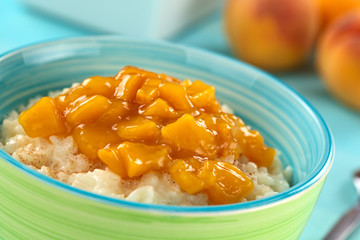 Colorful bowl full of rice pudding with peach compote