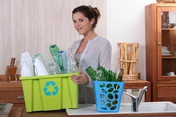 Brunette recycling empty bottles