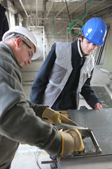 Two manual workers cutting sheet metal