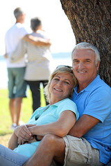 Mature couple leaning on tree trunk