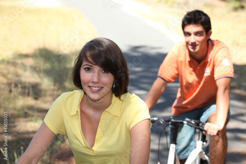 Young couple riding bikes in the country