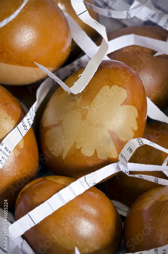 Decorated eggs with leaf pattern on shredded paper