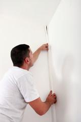handyman hiding a cable with a plinth