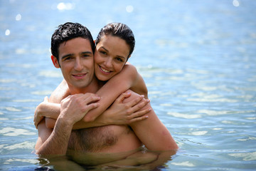 Young couple hugging in the water
