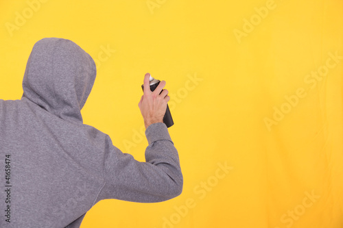 Man in a hoodie spray painting