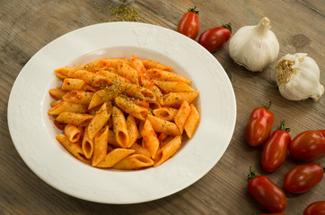 Penne pasta cooked with tomato sauce, garlic and oregano