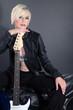 Hübsche blonde Frau mit E Gitarre blickt cool
