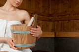 Woman with bucket at sauna