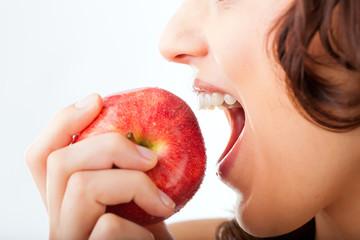 Junge Frau beißt in einen Apfel