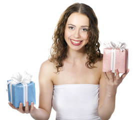 The beautiful girl smiling holds a gift in a boxes.