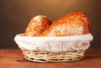 Baked bread in basket on wooden table on brown background