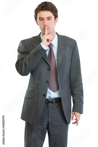 Modern businessman showing shh gesture